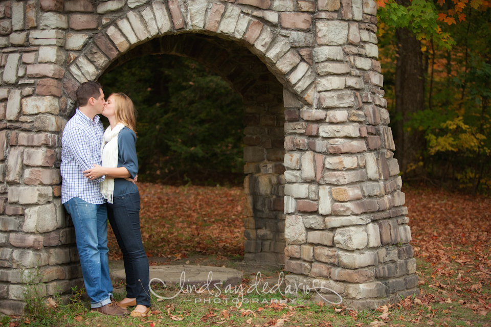 couple kisses under sculpture in Chestnut Ridge Park during their engagement portrait photo in Orchard Park, NY