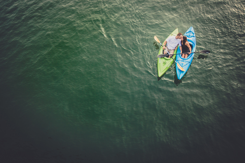 aerial engagement photography of couple kissing in kayaks in buffalo ny