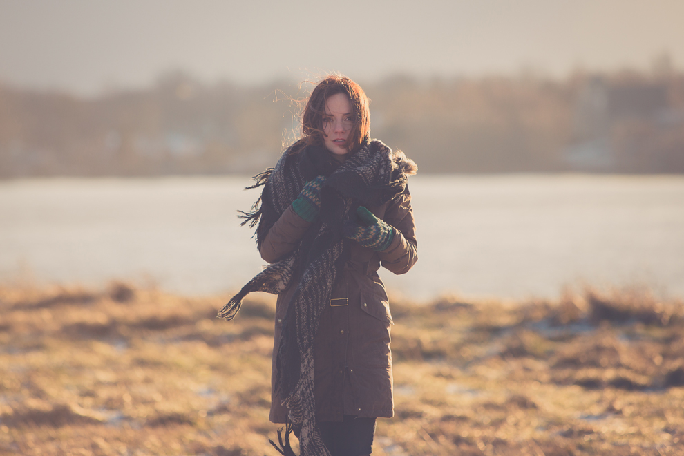 photograph of photographer Lindsay DeDario standing in field at Unity Island in Buffalo NY with the sunset behind her