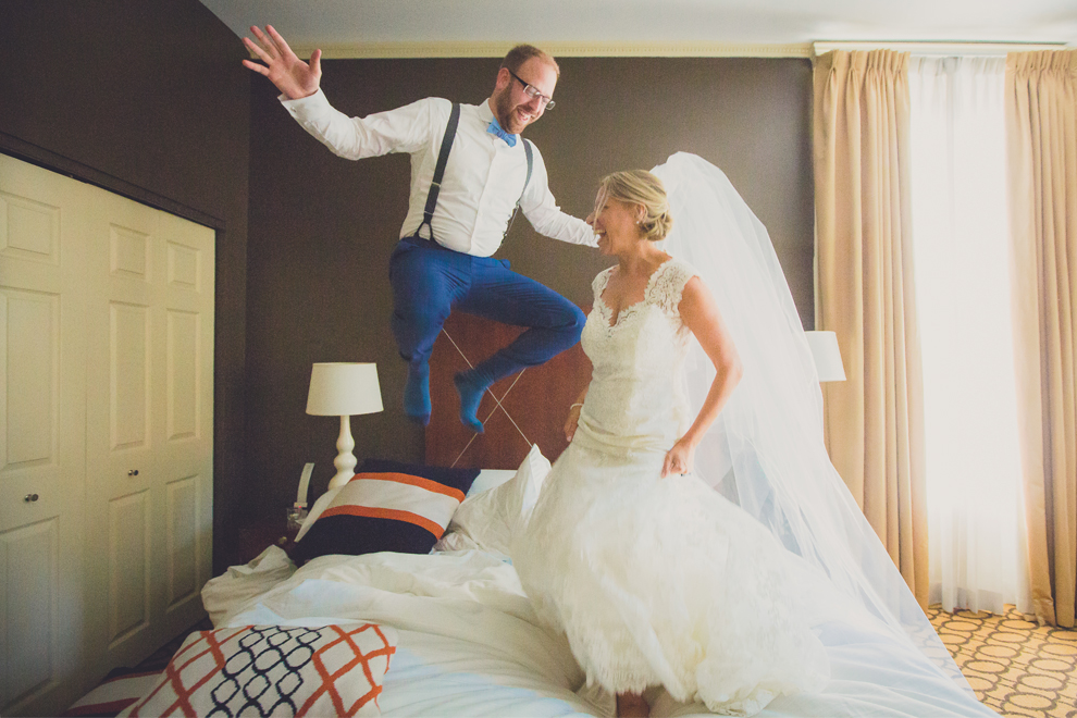 Bride and groom jump on bed in hotel room before their wedding reception at The Mansion on Delaware, a luxury boutique hotel in Buffalo, NY
