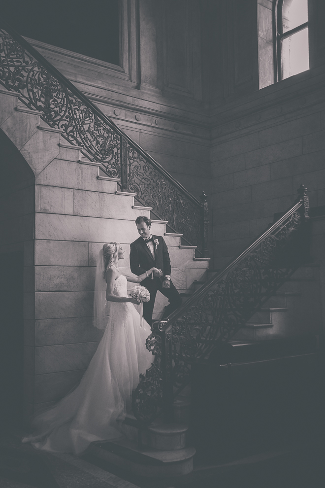 photography of groom escorting bride up stairs  by the hand on wedding day in dramatic side light at Ellicott Square Building in Buffalo, NY