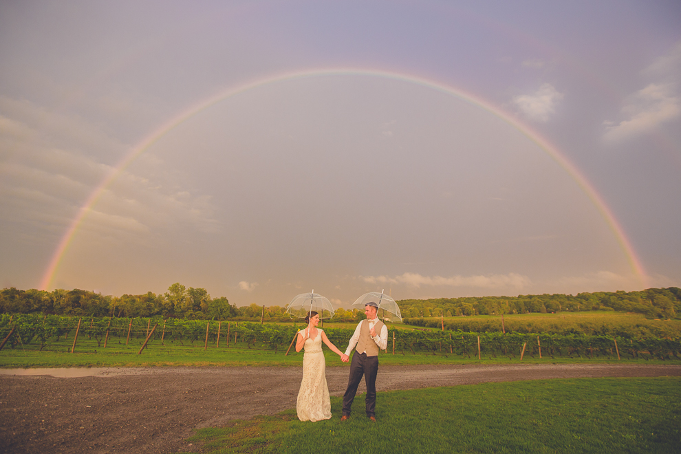 bride and groom stand hand in hand under clear bubble umbrellas beneath a double rainbow with a vineyard behind them on their wedding day at Freedom Run winery outside Buffalo, NY