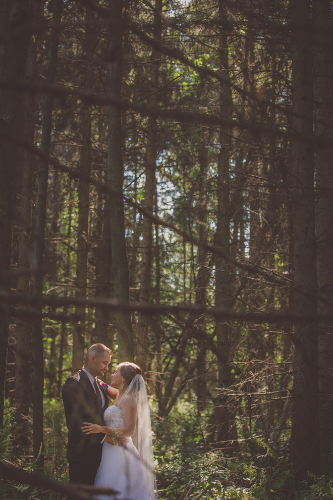 bride and groom gaze at each other in forest of Amherst State Park near Buffalo, NY on their wedding day