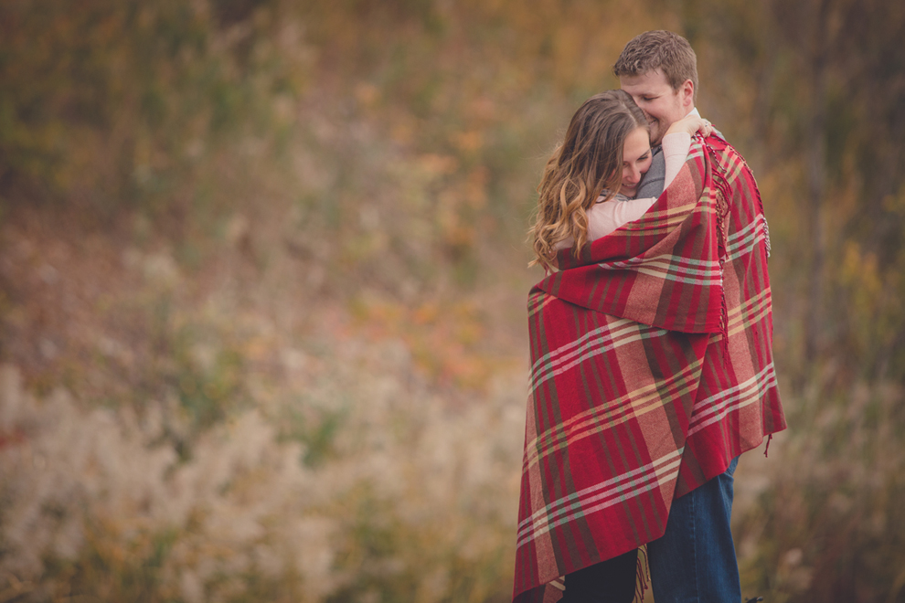 engagement photography of couple hugging wrapped in red plaid blanket on hiking trail at Lewiston Art Park near Buffalo, NY