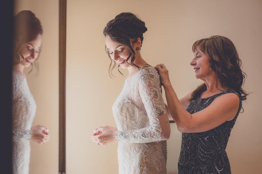 mother of bride helps daughter with wedding gown at Strathallan Hotel before George Eastman House Wedding Ceremony in Rochester, NY