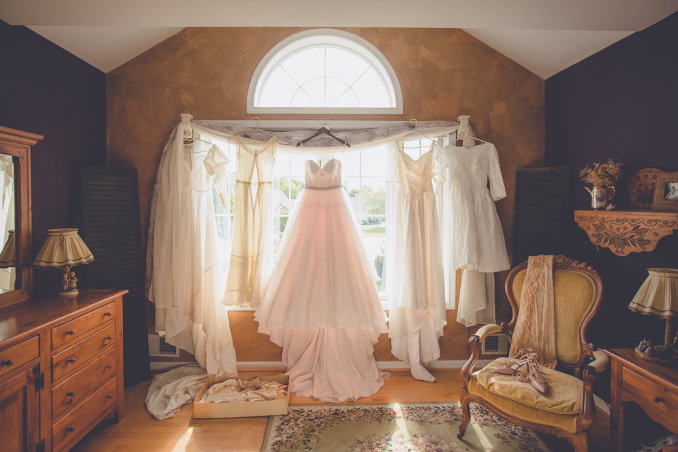 Six generations of wedding gowns pictured around bedroom window in Rochester, NY.  One dress is in a box on the floor, others hang from the curtain rod.