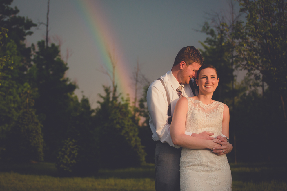 Bride and groom embrace beneath a rainbow on their wedding day at the columns banquets in Buffalo, NY