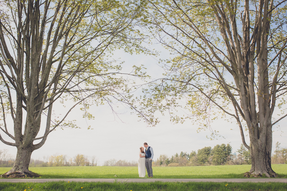 bride and groom stand on tree lined road while having their portraits taken during their wedding elopement at Knox Farm in East Aurora, NY