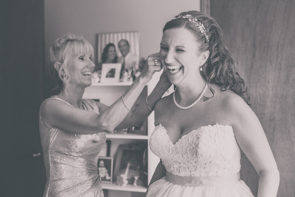 mother helps bride with earing before wedding in Buffalo, NY