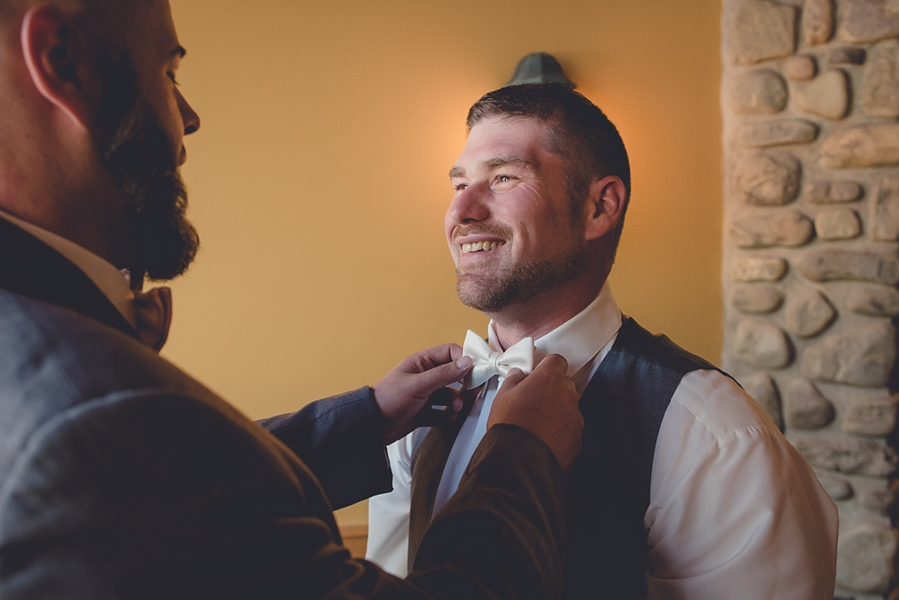 groom straightening bowtie at ski lodge wedding at holiday valley in ellicottville, ny