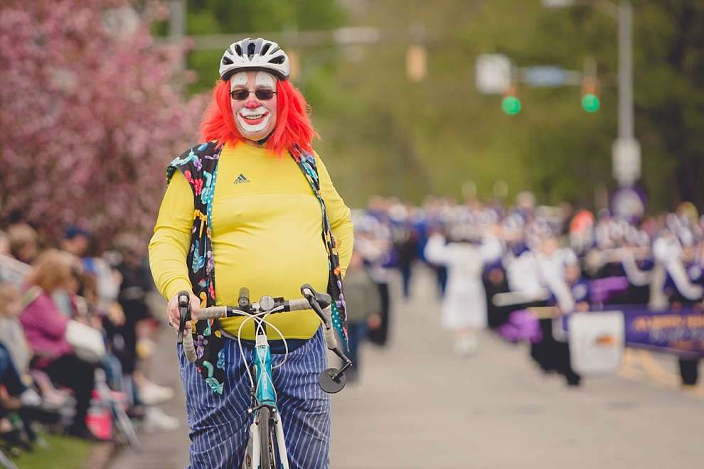 clown on bike poses for photo during parade at Lilac Festival at Highland Park in Rochester, NY