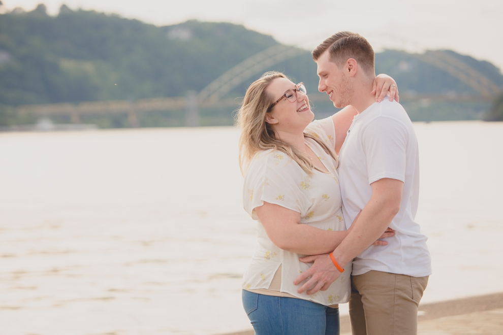 engagement photography of couple laughing in Point Park in Pittsburgh with bridge and river behind them