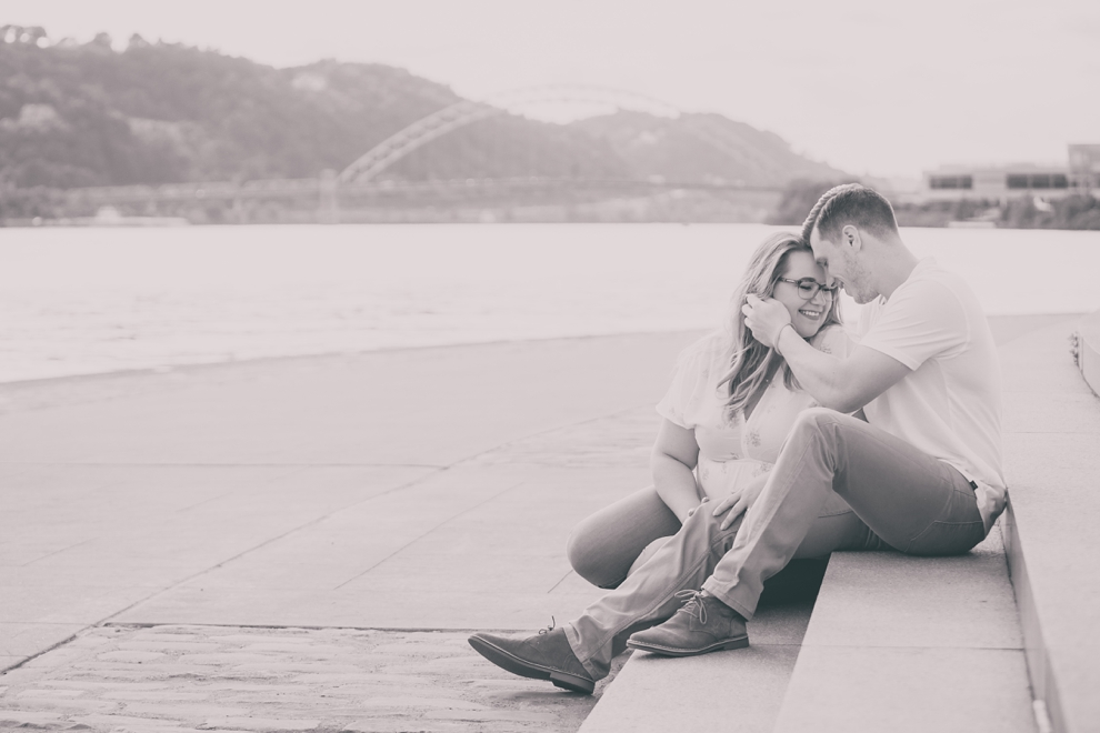 black and white engagement photography of couple sitting on steps in Point Park in Pittsburgh with bridge and river behind them