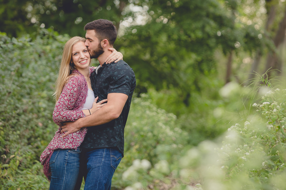 engagement photography groom kissing brides forehead in forest at Tifft Nature Preserve in Buffalo, NY