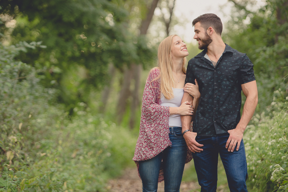 engagement photography of bride and groom looking at each other in forest at Tifft Nature Preserve in Buffalo, NY