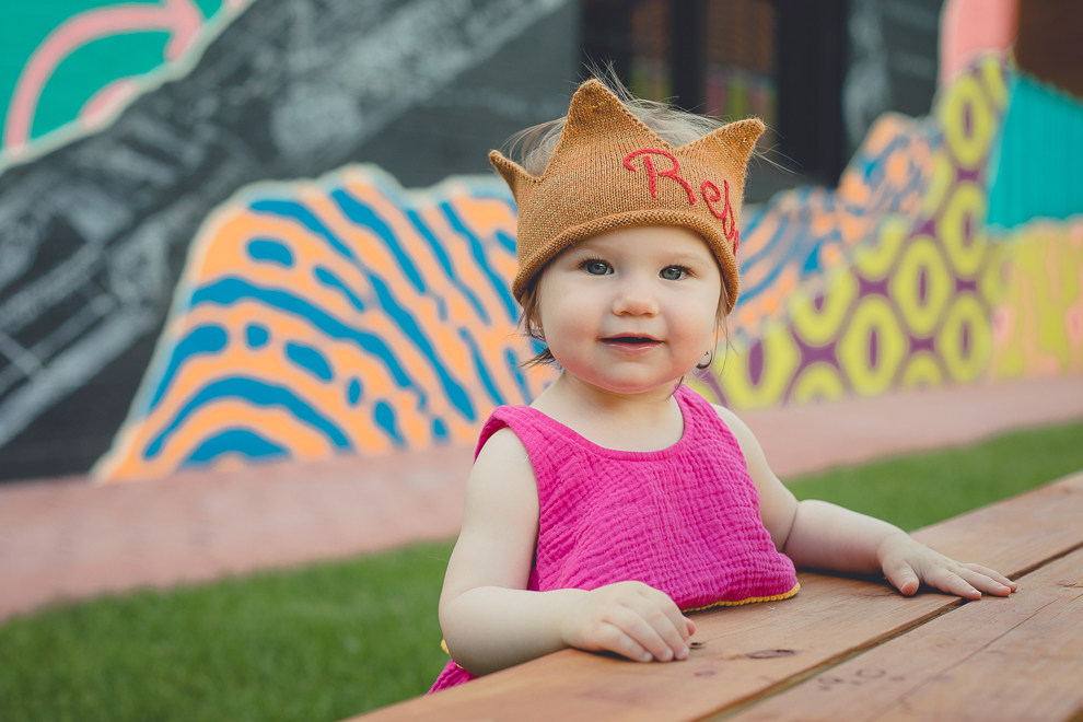 child smiles for photographer during family portrait photography session in front of murals on Chandler St. in Buffalo, NY