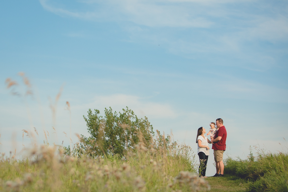 mom and dad stand with baby on top of hill in field during family portrait photography session in at Tifft Nature Preserve in Buffalo, NY