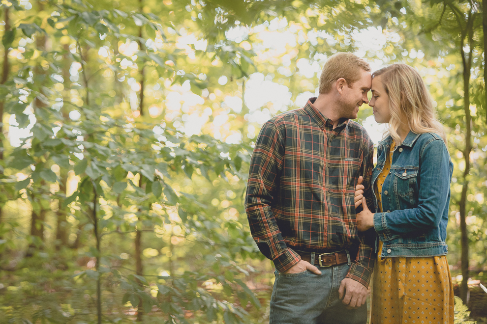 bride and groom pose for wedding engagement photos among fall foliage at their property in Ellicottville, NY