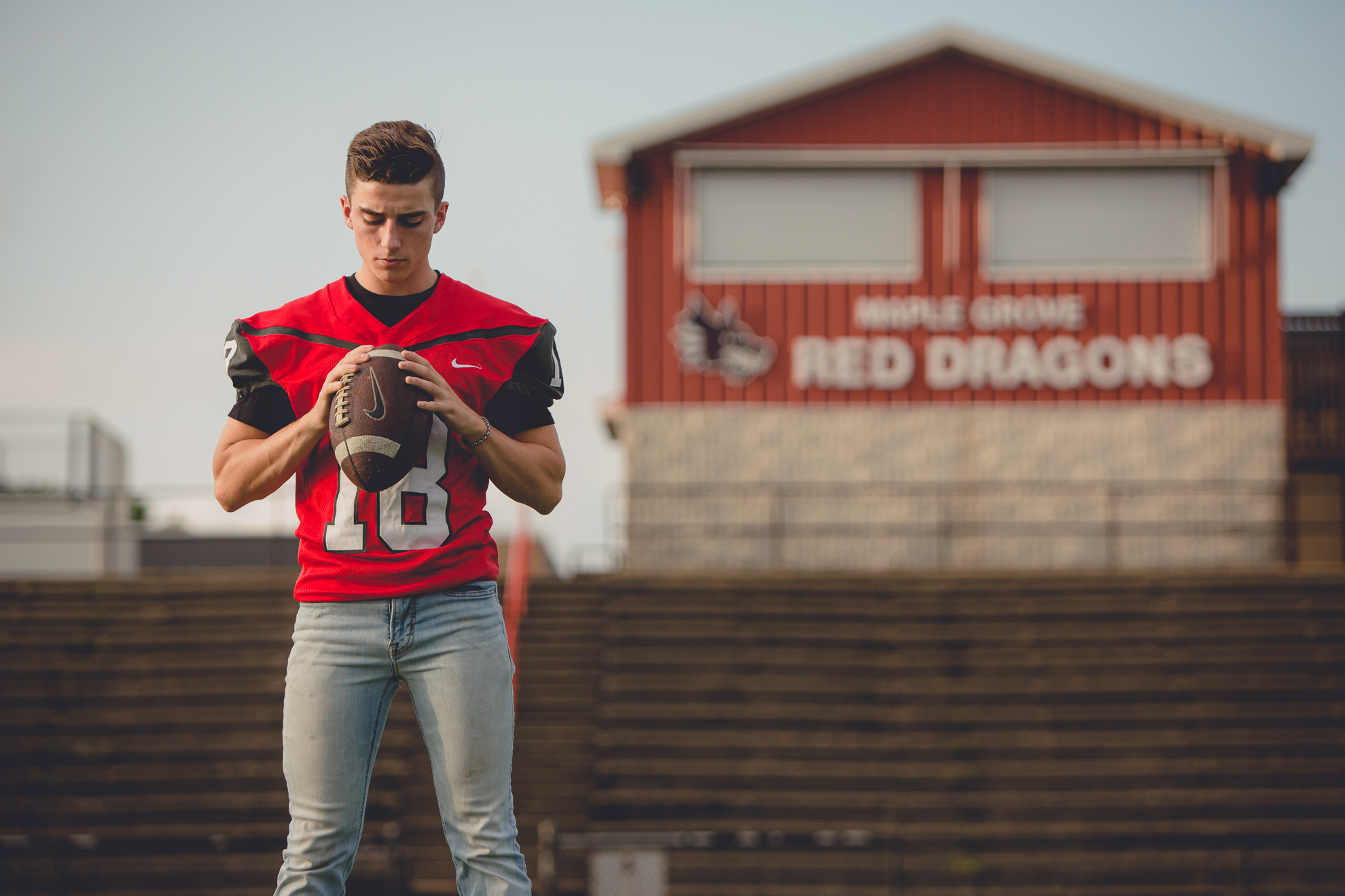 senior picture of football player on field holding ball at Maple Grove high school during portrait session near Buffalo, NY