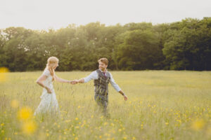 bride and groom hold hands as they walk through field at sunset during the reception of their small tented wedding at Knox Farm near Buffalo, NY in WNY