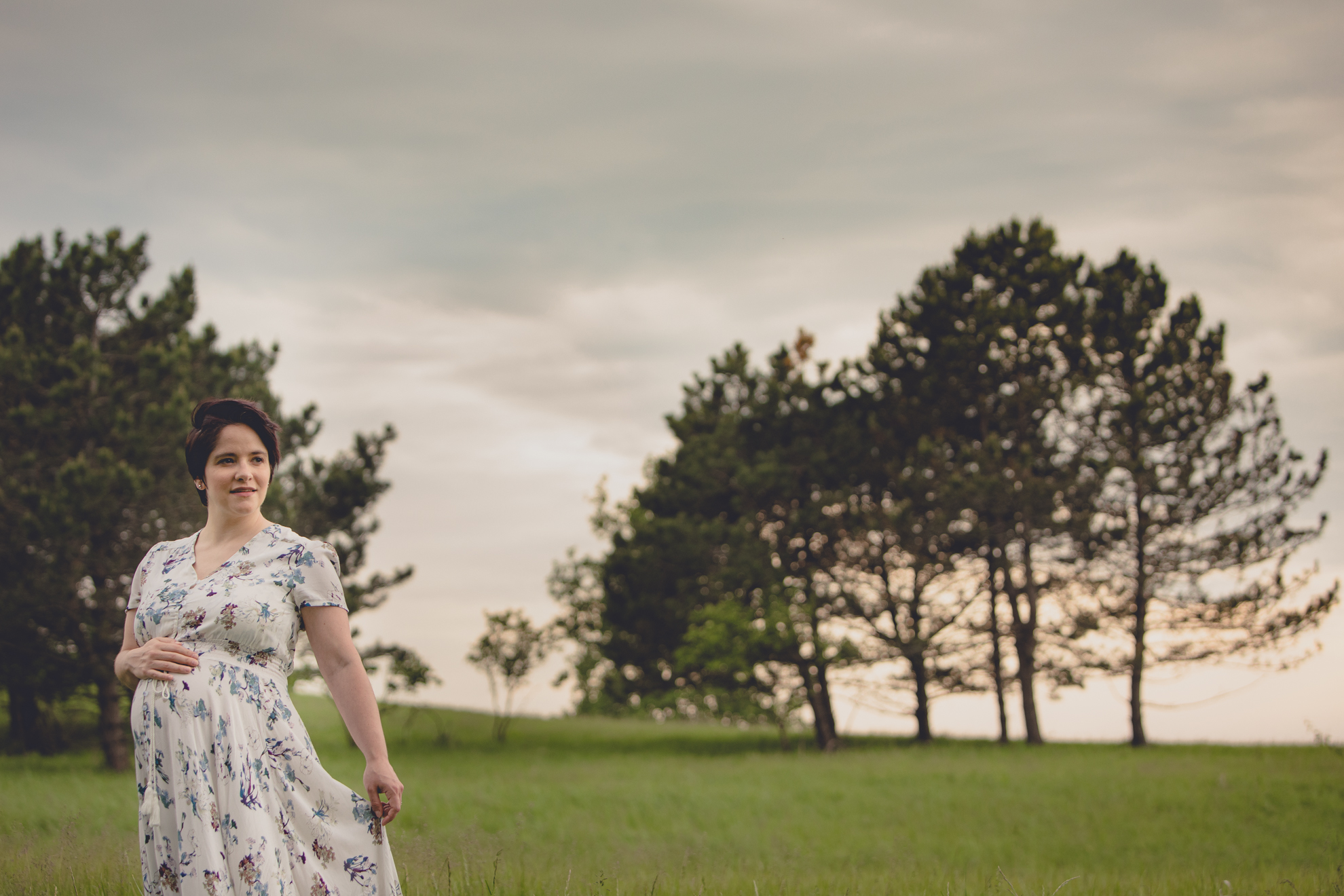 mom looks off to side while holding flowing dress during maternity portrait photography session in field at Tifft Nature Preserve in Buffalo, NY