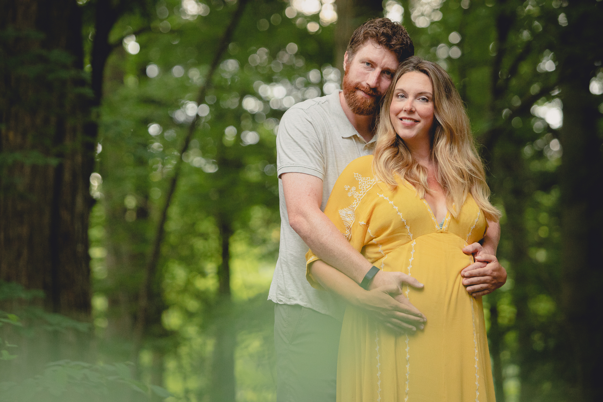 maternity portrait of pregnant mother with husband smiling for photographer in forest at Chestnut Ridge Park near Buffalo, NY