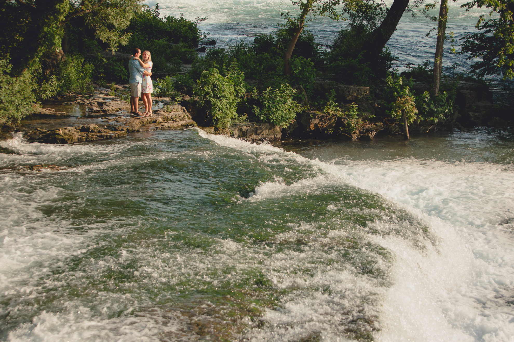 future bride and groom embrace in front of rapids on Goat Island during wedding engagement photography session in Niagara Falls State Park in NY