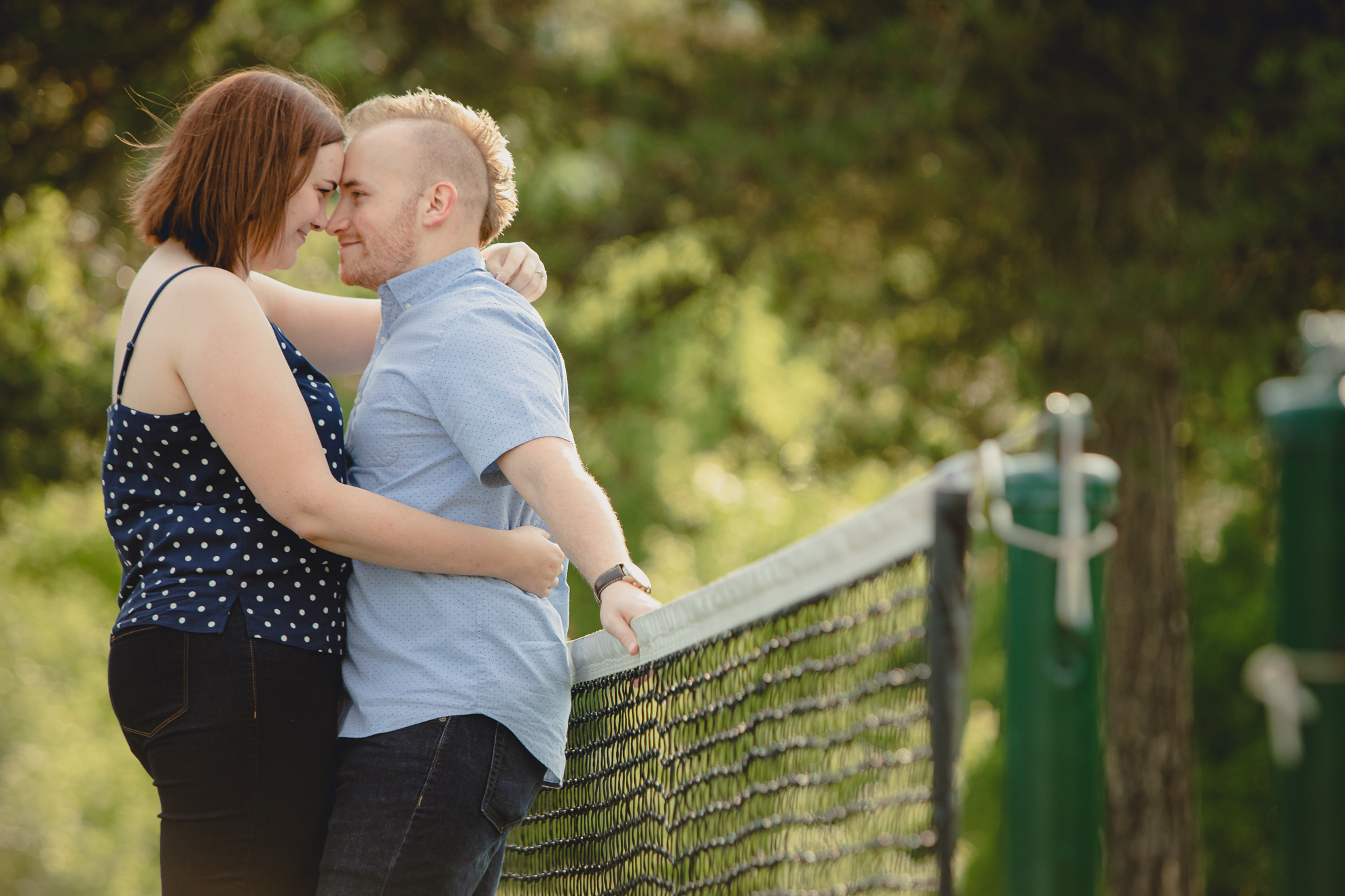 engaged couple poses for photographer with foreheads touching while leaning against a tennis net at Akron Falls Park near Buffalo, NY