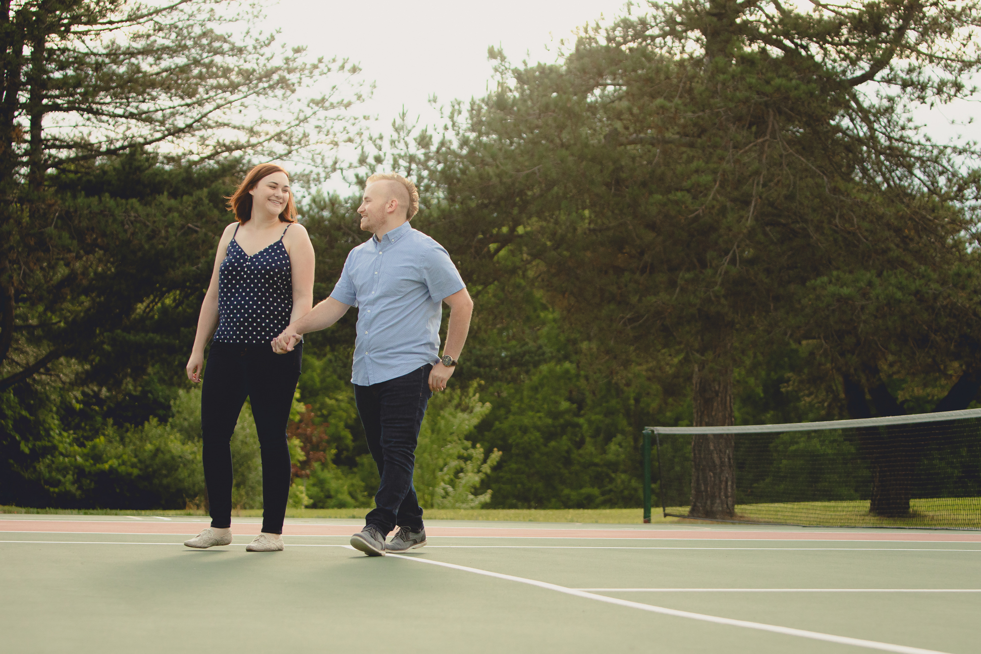 engaged couple walks together on tennis court at Akron Falls Park near Buffalo, NY