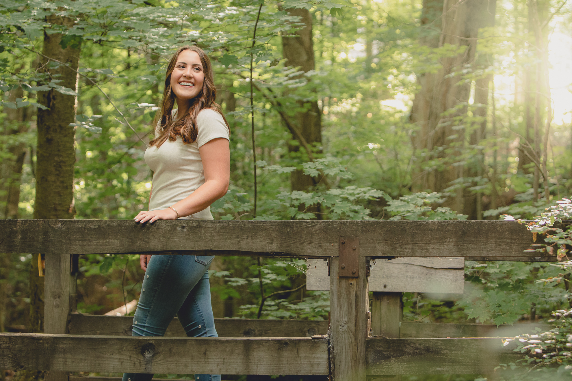 Tessa laughs on bridge during senior portrait photography session in Long Point State Park in WNY