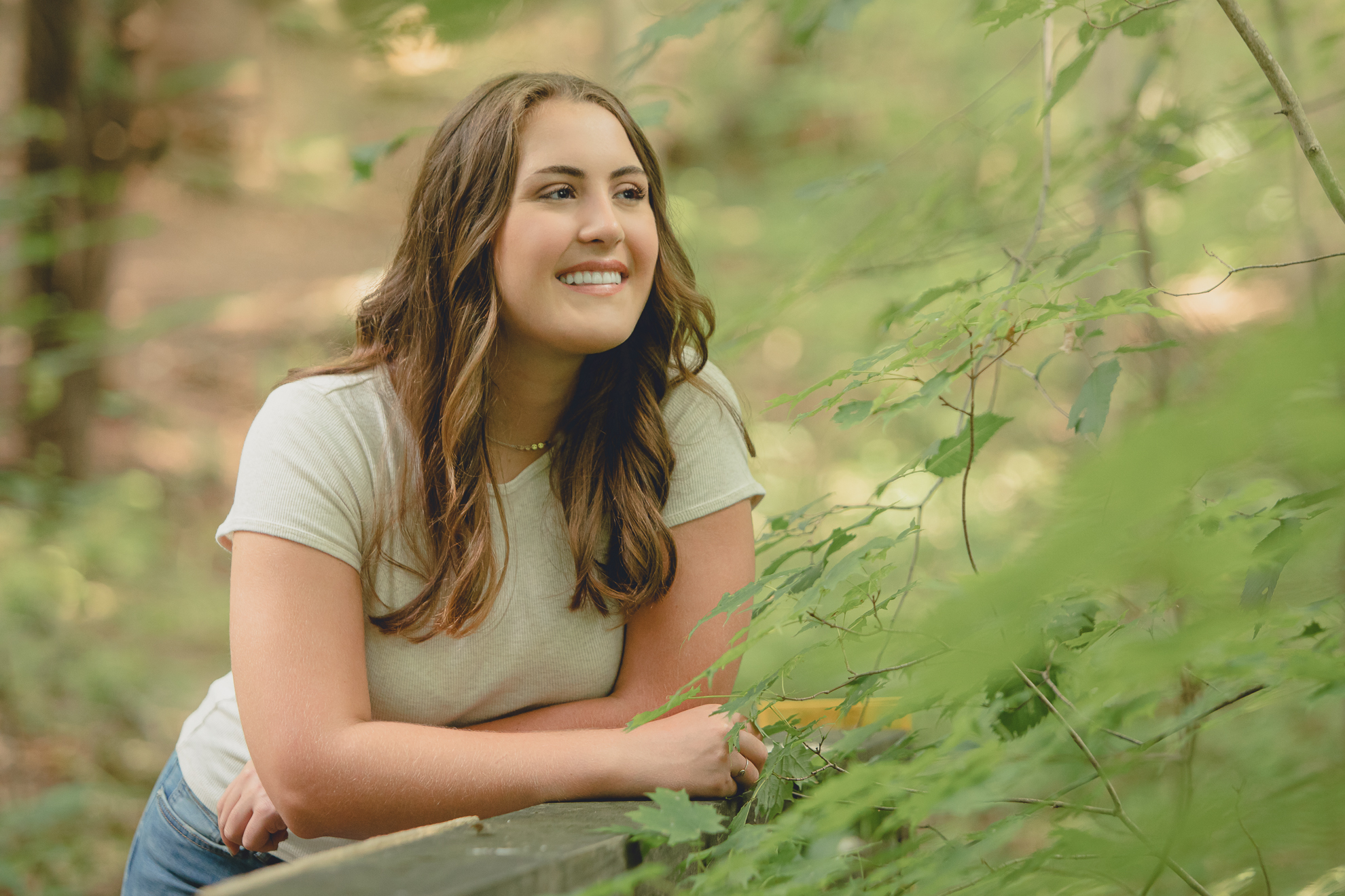 tessa smiles while leaning on bridge during senior portrait photography session in Long Point State Park in WNY