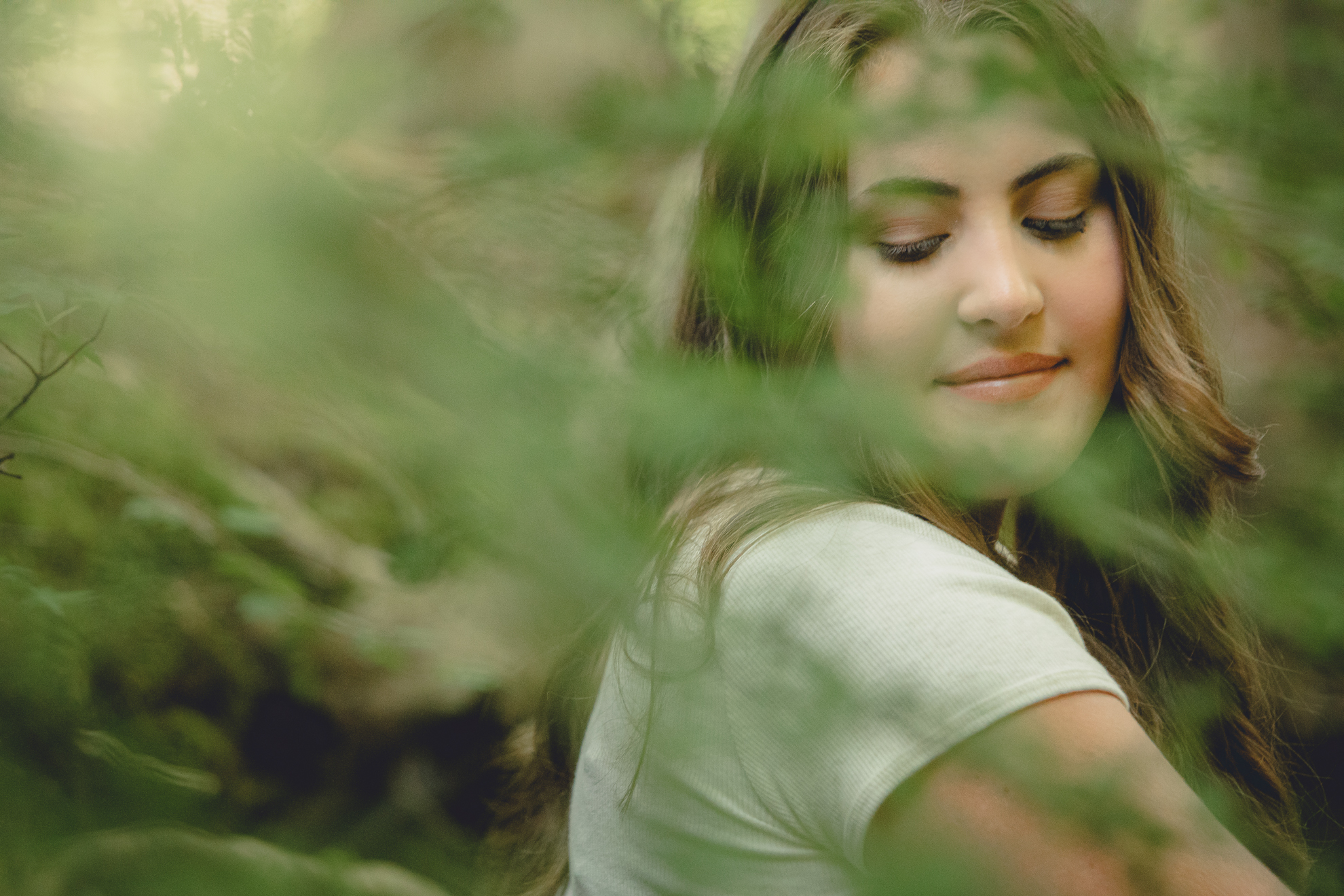 Tessa looks over shoulder in woods during senior portrait photography session in Long Point State Park in WNY