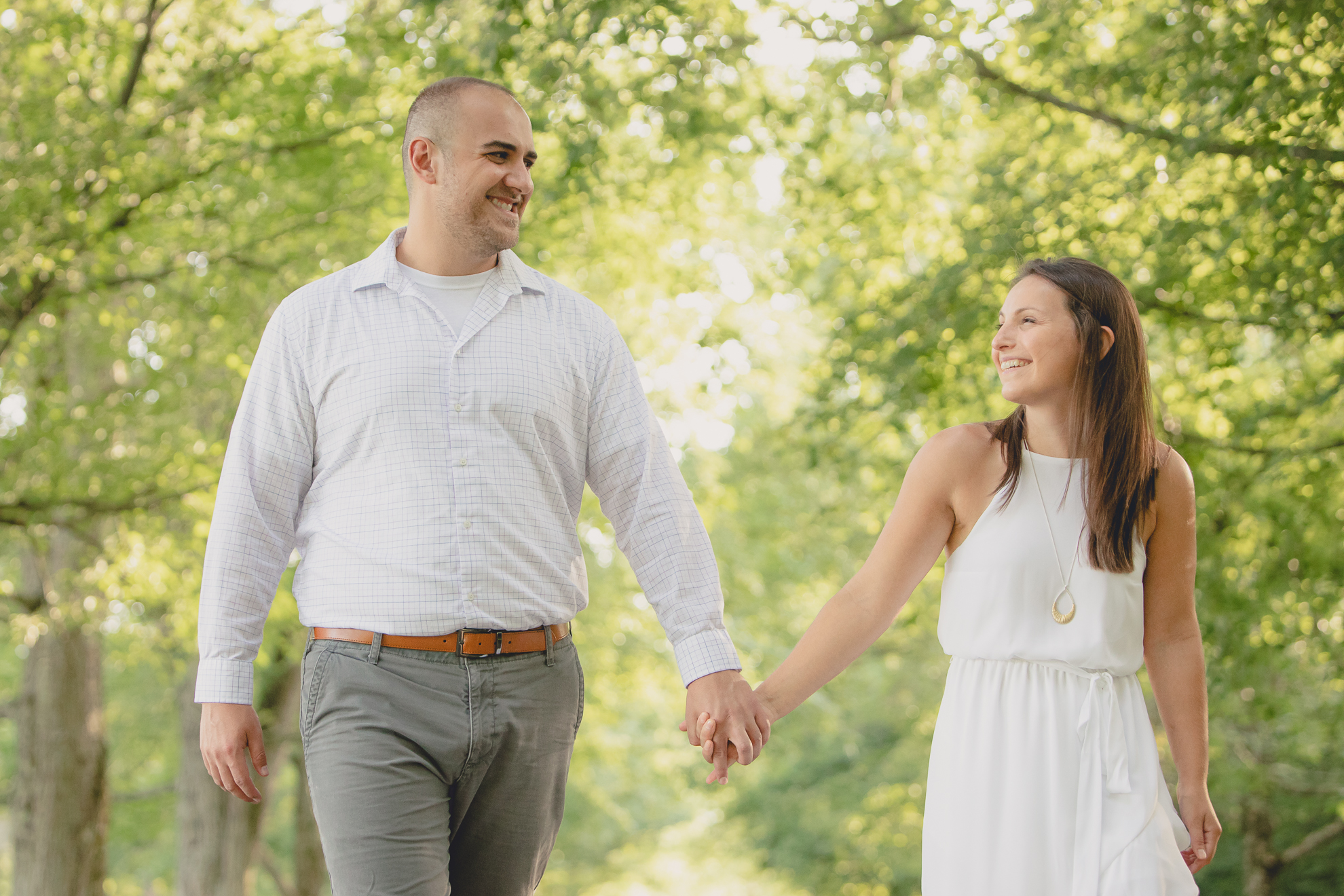 bride and groom laugh and hold hands while walking down tree lined road during wedding photography engagement portrait session at Knox Farm near Buffalo, NY