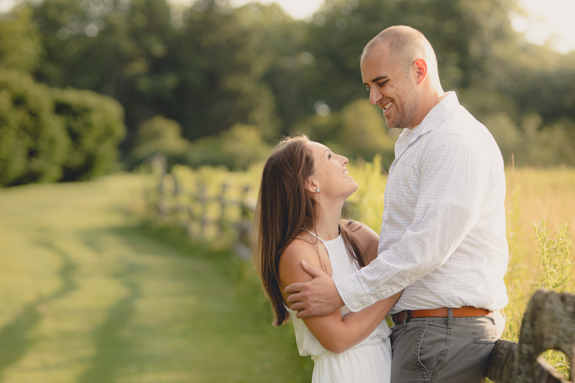 bride and groom laugh during wedding photography engagement portrait session in field at Knox Farm near Buffalo, NY