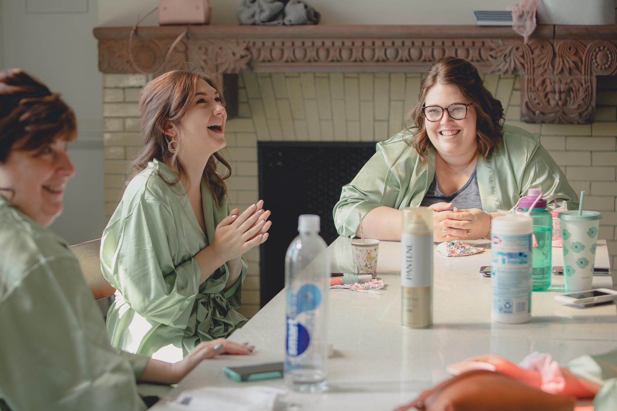 bridesmaids laugh at table before wedding at Hotel Henry in Buffalo, NY