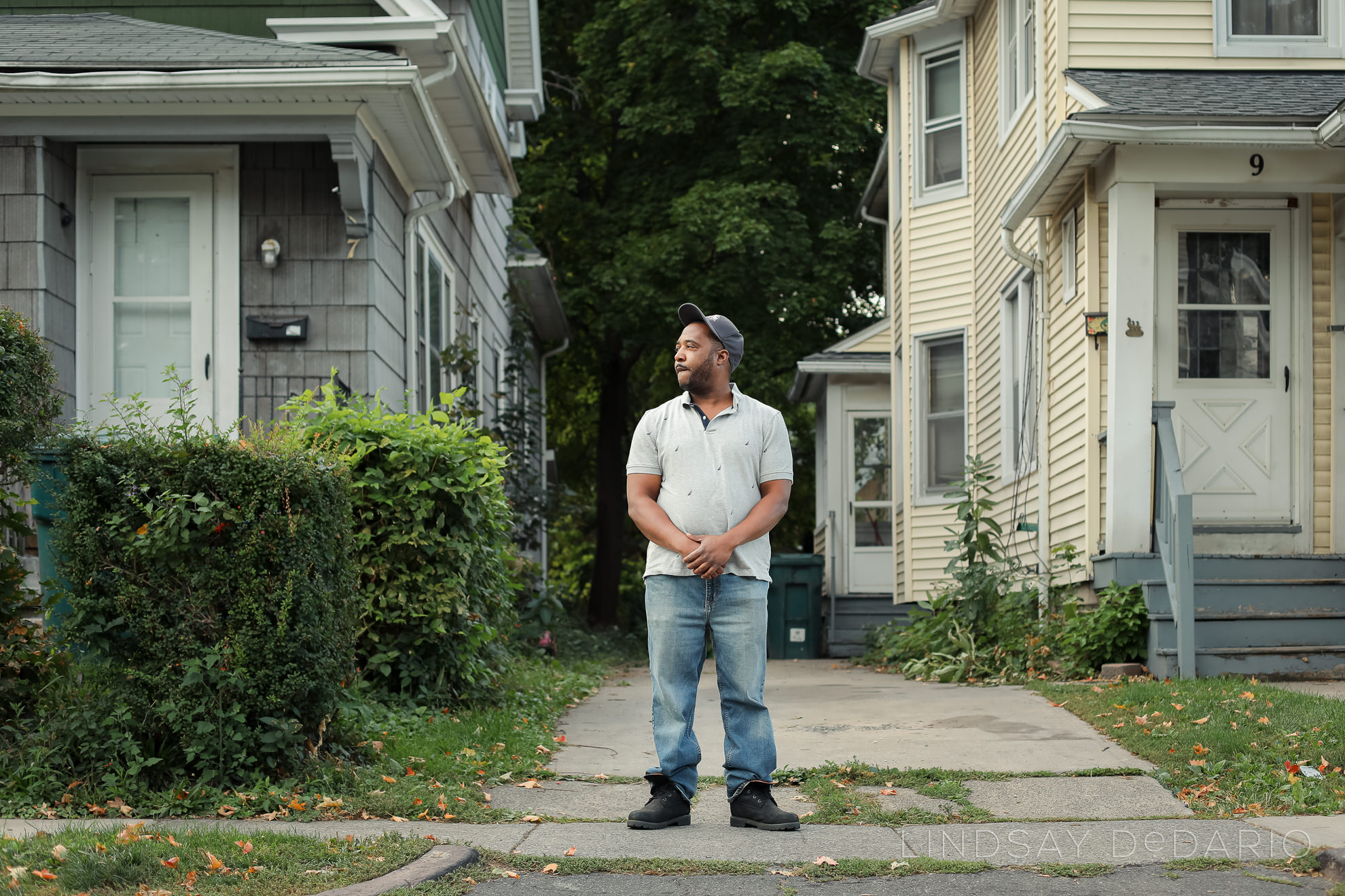 Silvon Simmons poses for portrait in front of driveway where he was shot by police in Rochester, NY