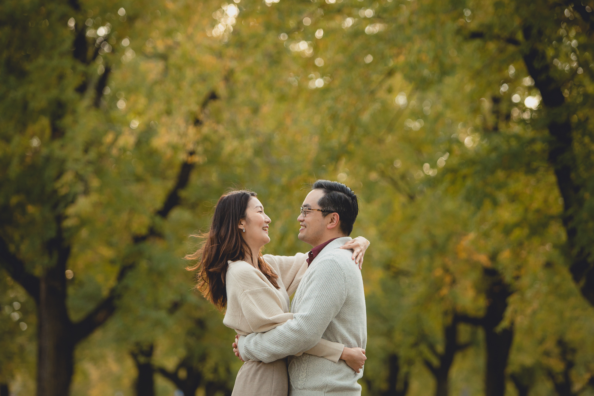 bride and groom pose for engagement photos among fall foliage in Bidwell Parkway in Buffalo, NY