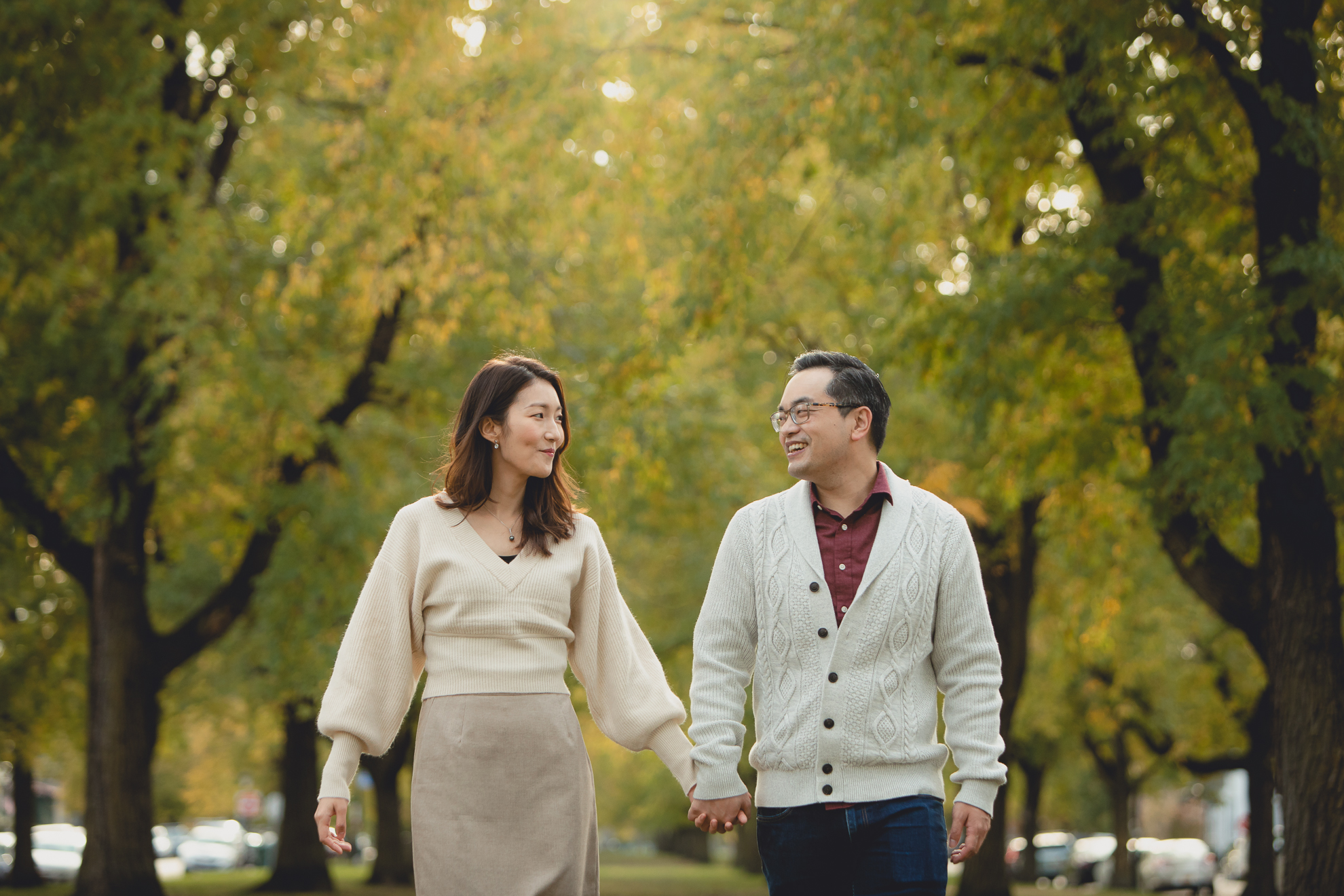 bride and groom walk holding hands during engagement photography session among fall foliage in Bidwell Parkway in Buffalo, NY