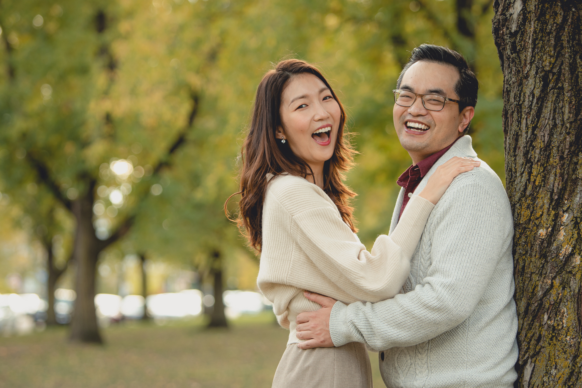bride and groom laugh during engagement photos among fall foliage in Bidwell Parkway in Buffalo, NY