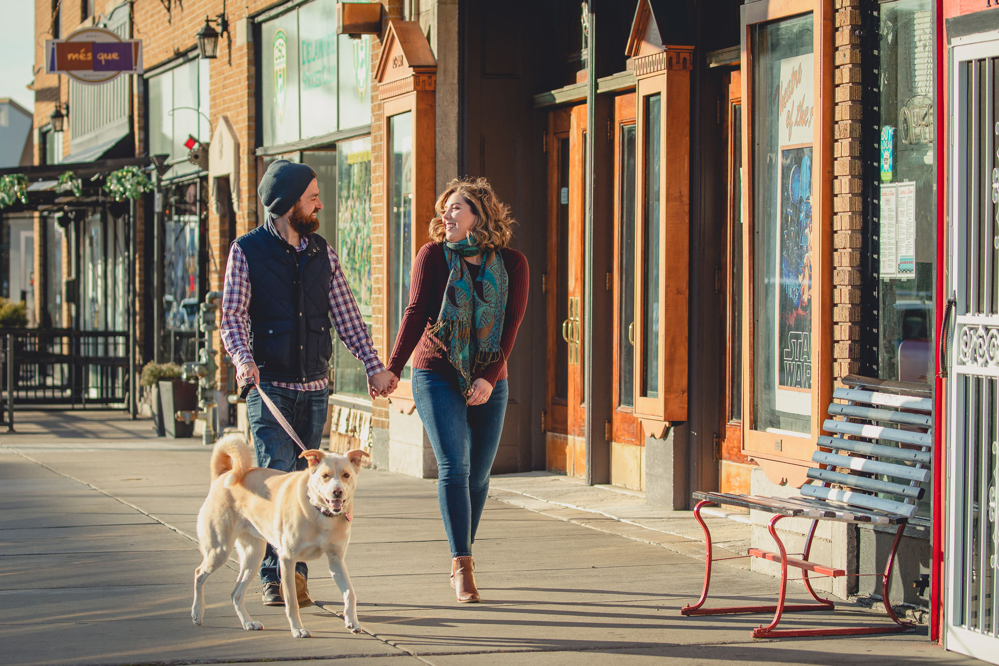 couple walks dog in front of North Park Theater during couples mini photography session on Hertel Ave. in North Buffalo, NY
