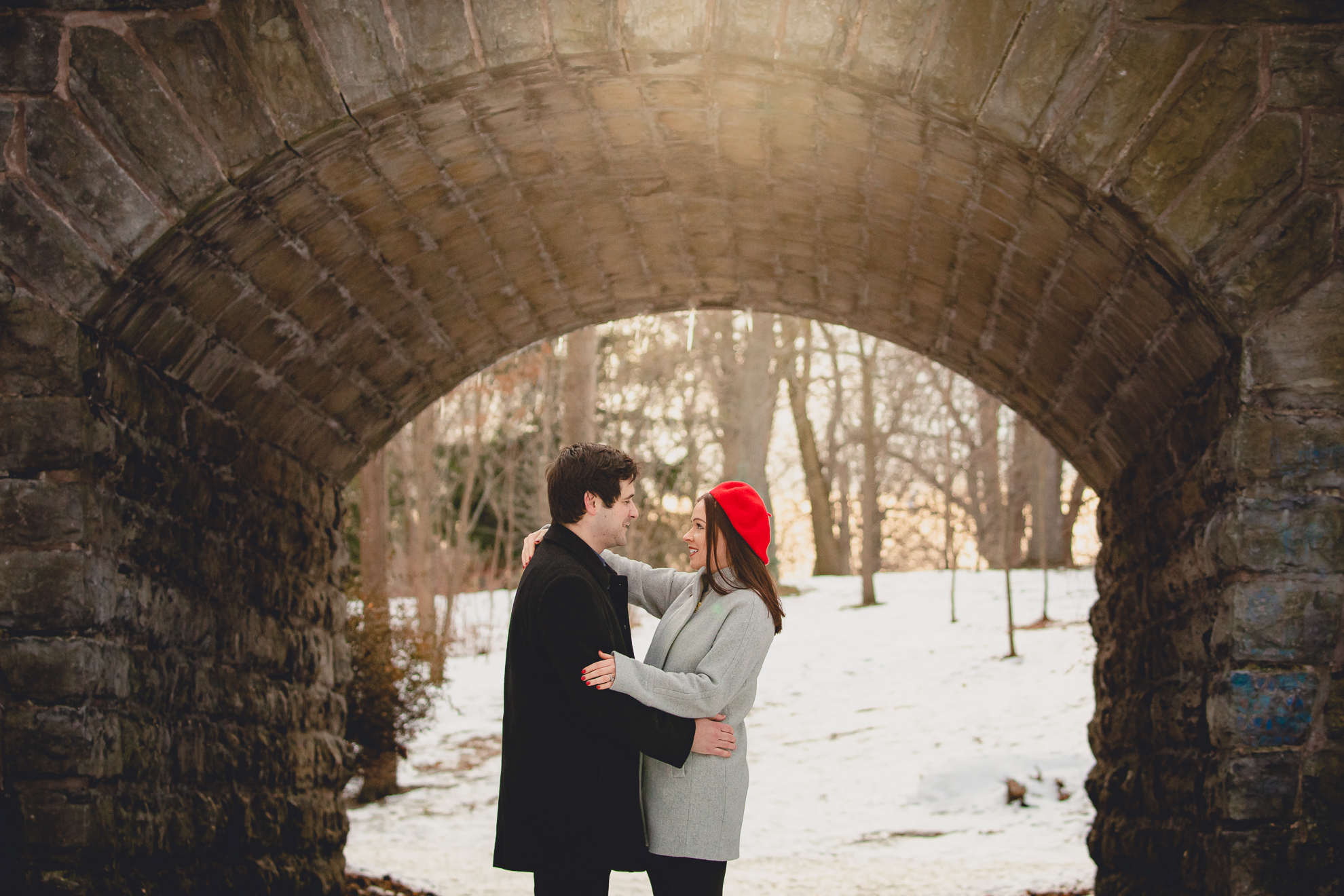 bride and groom smile at one another in front of the Ivy Bridge in Delaware Park during their wedding engagement photography session in Buffalo, NY