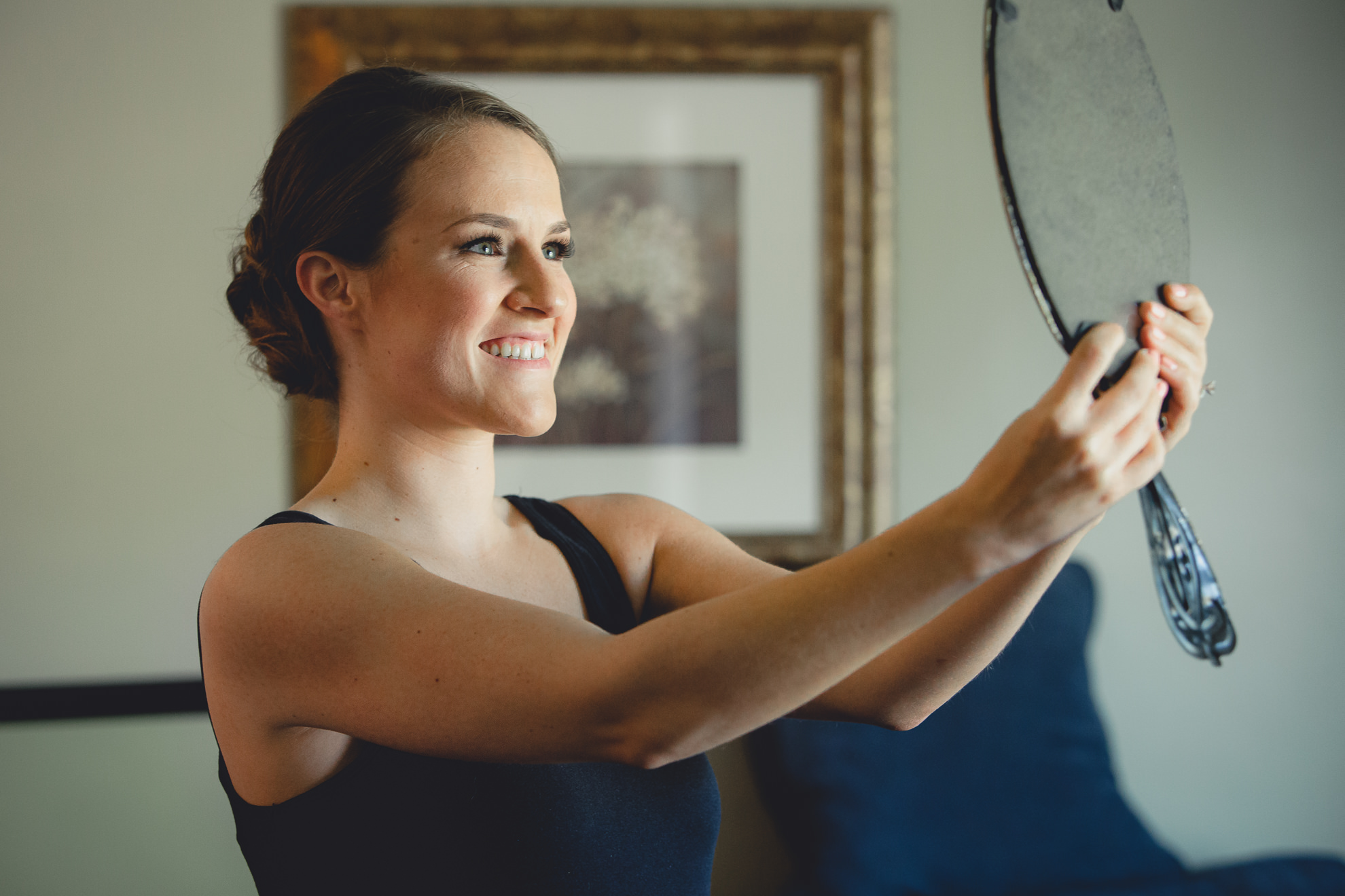 bride looks at self in mirror before wedding ceremony in Buffalo, NY