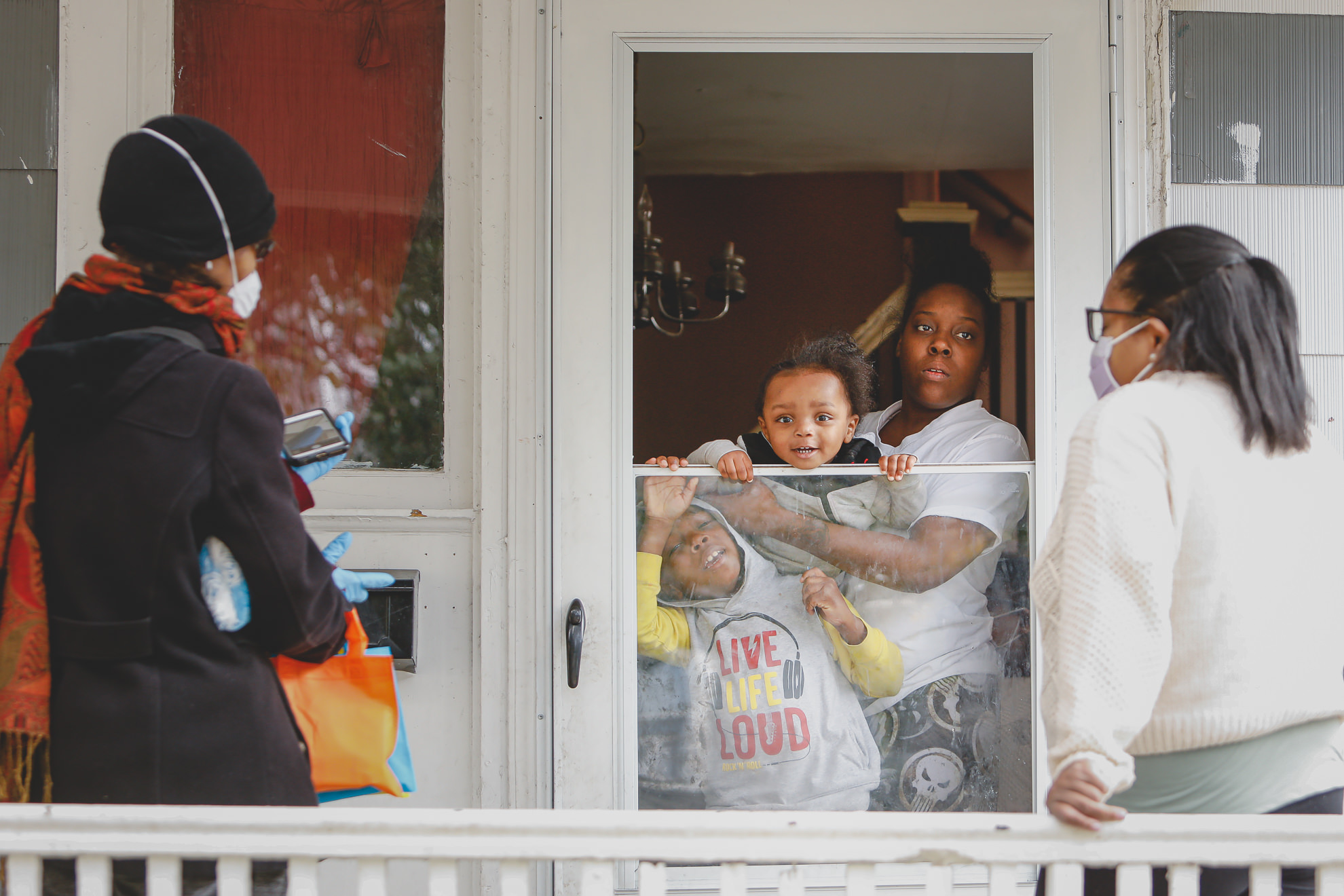 Sister Jenthia Abell and Dr. Angela Branche hand out coronavirus disease (COVID-19) survival kit to Natalie Hall as part of a door-to-door outreach program to the Black community to increase vaccine trial participation in Rochester, New York