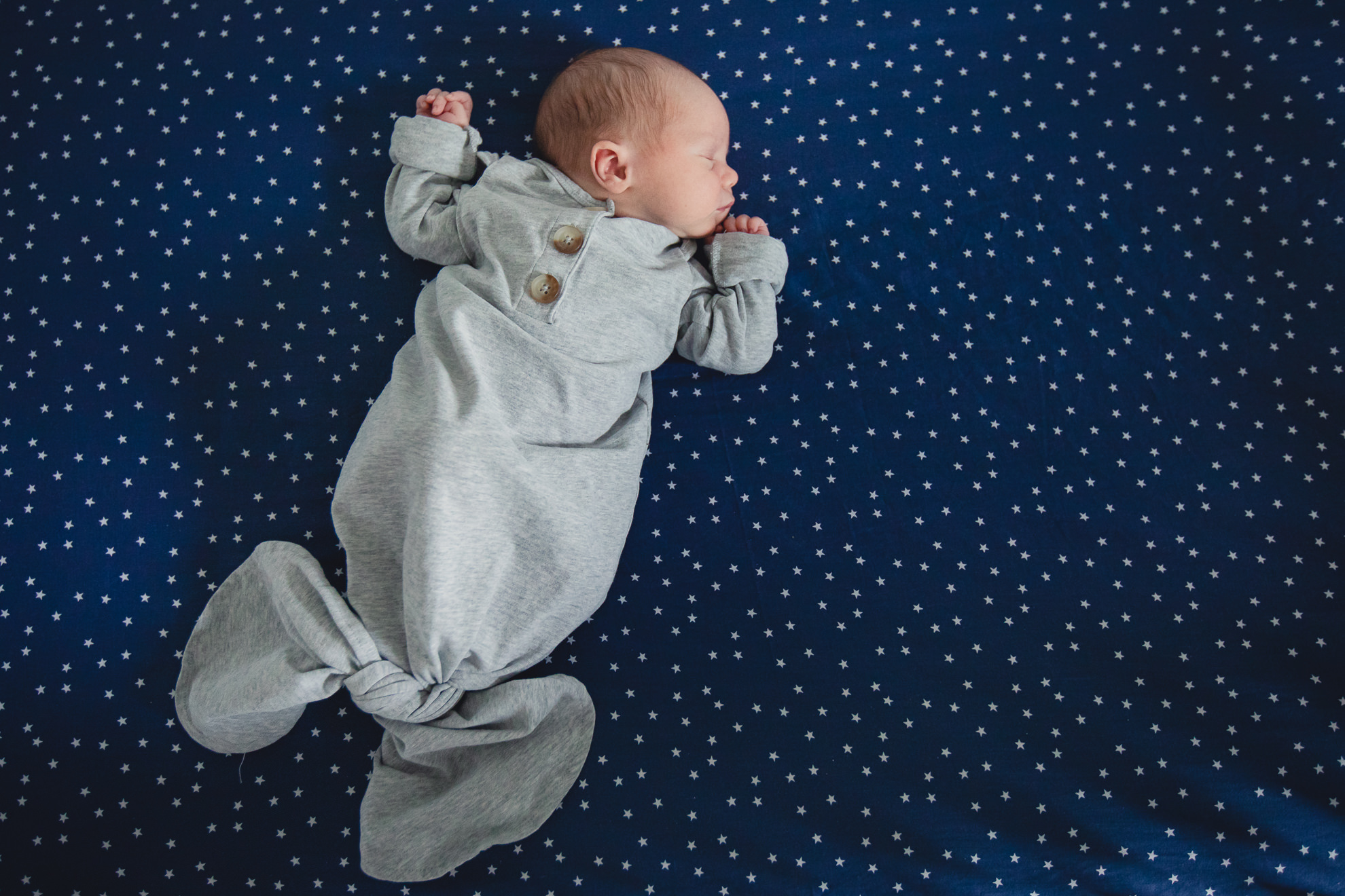 baby lies on star backdrop during newborn baby family photography session in Buffalo, NY